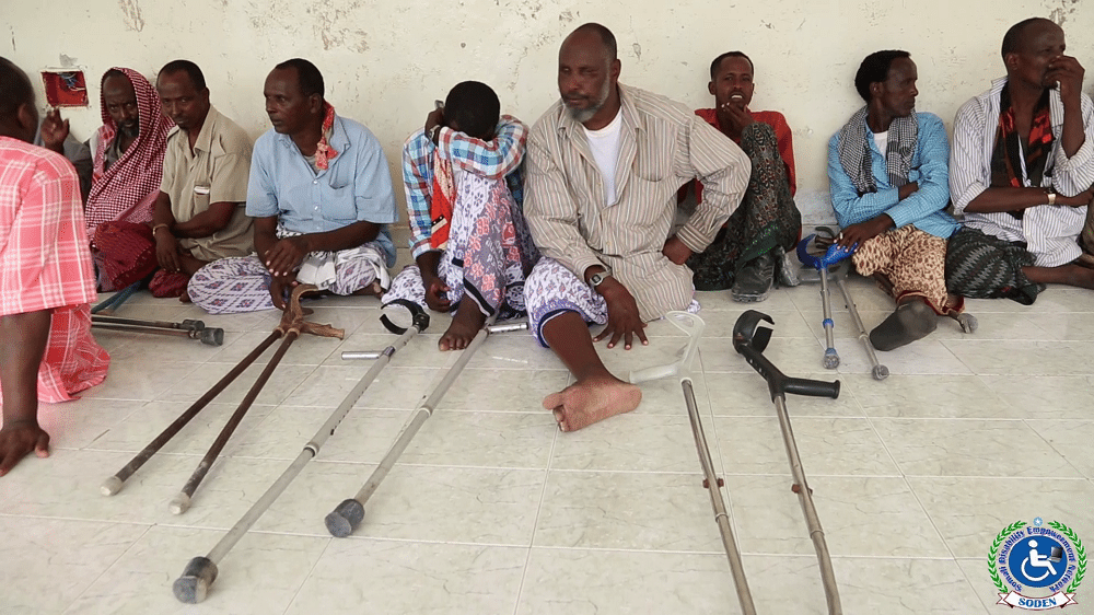 Beneficiaries sat on the floor with crutches in front of them