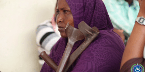 Female beneficiary looking left holding her crutches