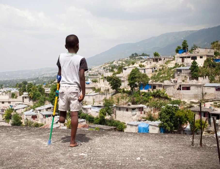 Disabled child with crutches looking at village from distance