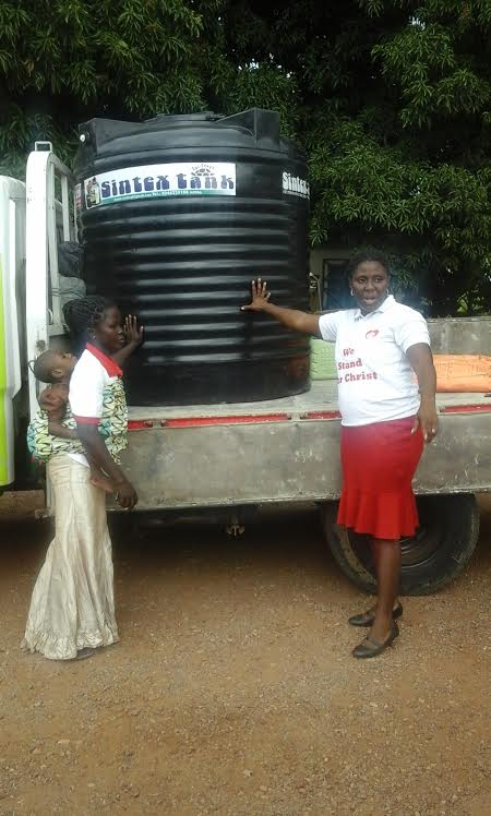 Ms Rosemary Ladzi receiving a Poly-tank from the NGO