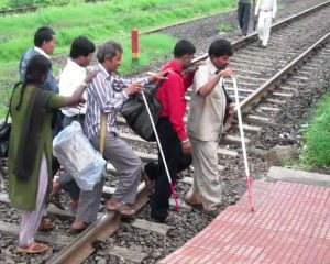 People with visual impairment crossing the railway track in India