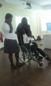 Child in wheelchair speaking on microphone surrounded by two women