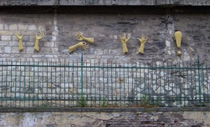 Mannequin hands signing stuck on wall as art work