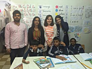 Khizran (left), a student stands at the back with 3 young students (female). Sitting in front are three children with hearing impairments.